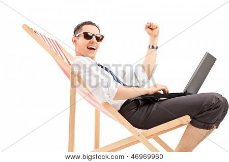 Young professional man sitting on a beach chair with a laptop and expressing happiness, isolated on white background