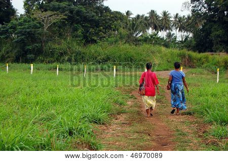 Two Women Walk At Gravel Road