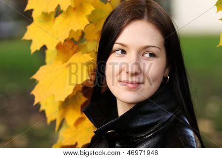 Beautiful brunette woman with golden autumn leaf