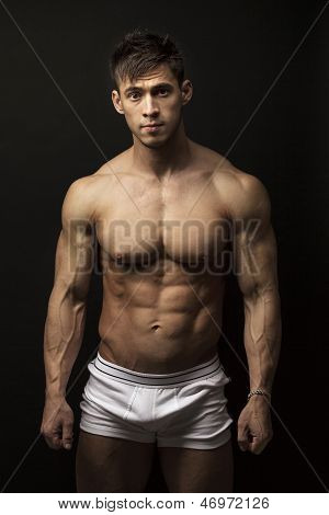 Muscular young man over black