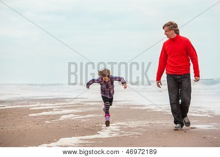 Dad and cheerful 6 years old girl walking along the seacoast
