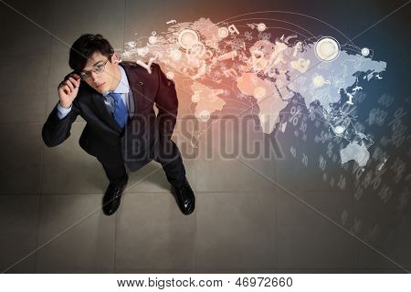 Top view of young businessman making decision against global network back