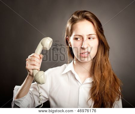 stressed young woman holding a telephone