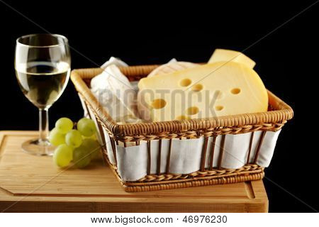 White wine in fine glass with cheese and grape
