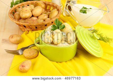 Concursos jovens batatas com creme de leite e ervas no pan em close-up de madeira mesa