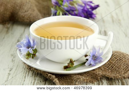 Cup of tea with chicory, on wooden background