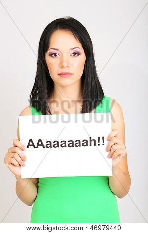 Surprised young woman holds inscription