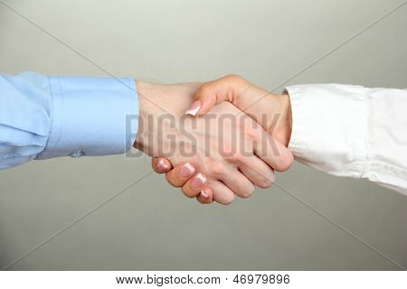 Business handshake on gray background