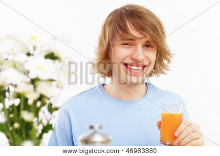 Young happy man smiling and drinking juice