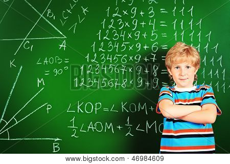 Portrait of a smiling schoolboy standing over blackboard.