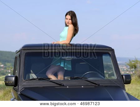 Happy Young Woman Getting Out The Car's Sunroof