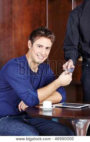 Young man in caf���© paying his coffee with a credit card
