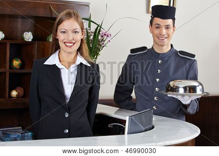 Happy concierge and receptionist in hotel waiting at counter