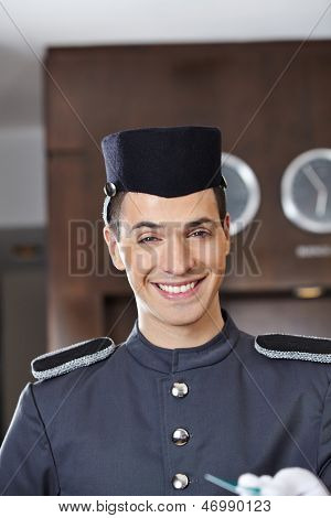 Happy hotel concierge smiling with key card in his hand