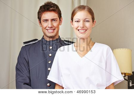 Portrait of bellboy and hotel maid in a hotel room