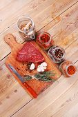picture of peppercorns  - raw beef meat fillet with peppercorn and thyme and different spices in glass bottles ready to grill on wood figured aged board over table - JPG