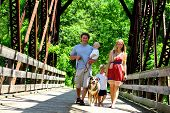 image of covered bridge  - A young attractive family of four people walking across a bridge - JPG