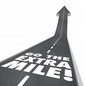 image of mile  - The words or saying Go the Extra Mile on a road with arrow going upward to illustrate improvement - JPG