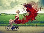 stock photo of bike path  - beautiful girl goes by bicycle with red dress - JPG