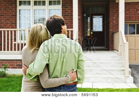 Happy Couple In Front Of Home