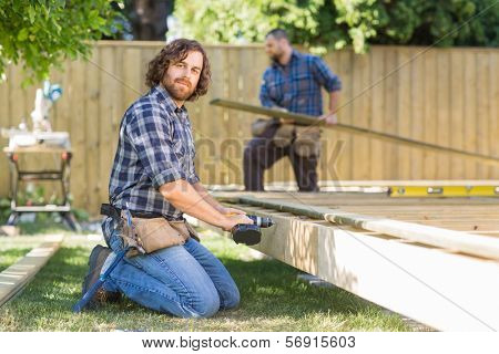 Portrait of confident mid adult manual worker drilling wood with coworker working in background at construction site