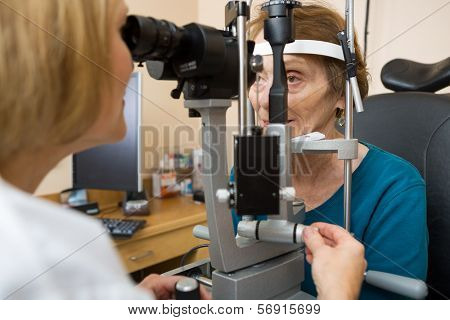 Female optometrist examining senior woman's eyes with slit lamp in eye clinic