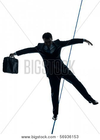 one caucasian Businessman tightrope walker in silhouette studio isolated on white background