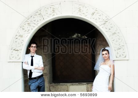 Bride And Groom Under White Arch