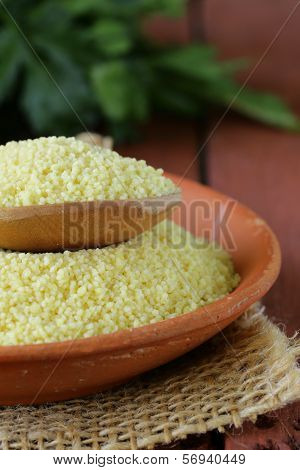cous cous cereal in a clay bowl on wooden table