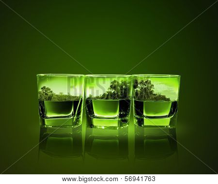 Three glasses of green absinth with nature illustration in