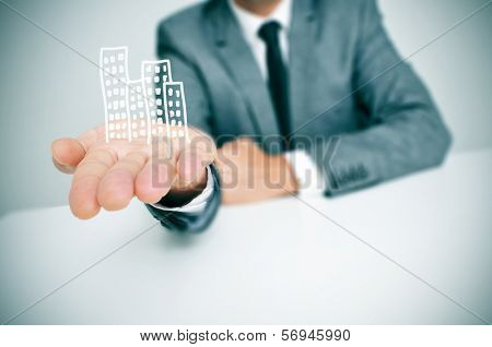 a businessman sitting in a desk showing a pile of drawn buildings in his hand