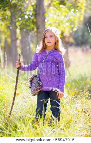 Hiking kid girl with walking stick in autumn poplar trees forest