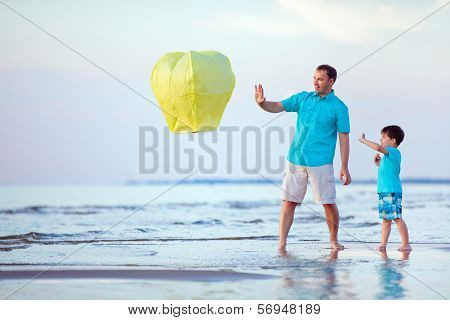 Happy father and son flying fire lantern together