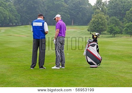 Golfer and caddy on the fairway of a par 4 reading the course guide for club selection.