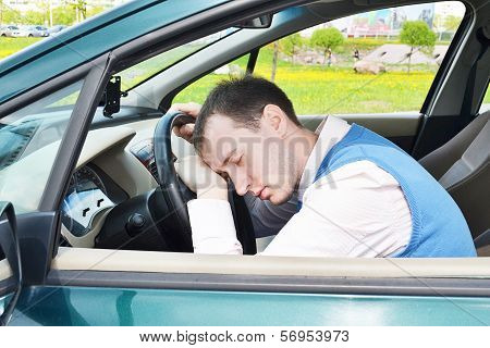 man sleeps in a car