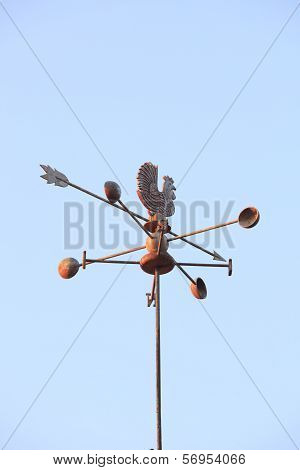 Weather Vane Compass Over House Roof Against Blue Sky Background With Copy Space