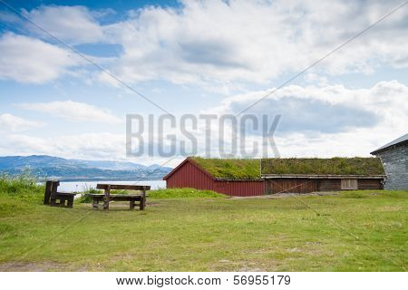 Houses With Grass Covered Roofs And Benches Near A Fjord