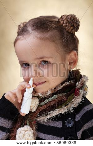 Little girl with nasal spray - fighting cold and the flu