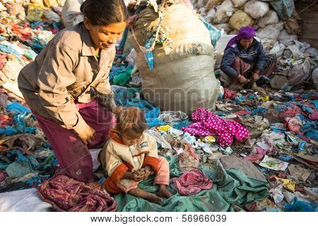 KATHMANDU, NEPAL - DEC 22: Unidentified child is sitting while her parents are working on dump, Dec 22, 2013 in Kathmandu, Nepal. In Nepal annually die 50,000 children, in 60% of cases -malnutrition.