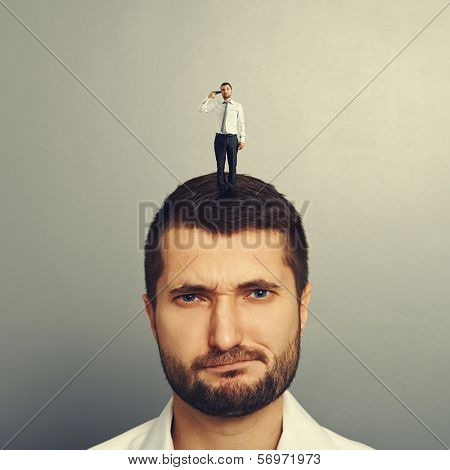 dissatisfied man with small unhappy man on the head