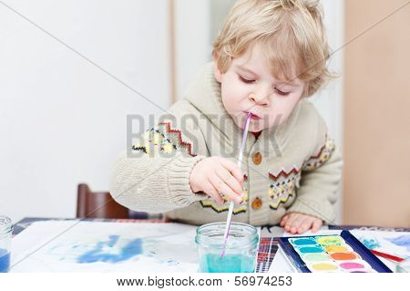 Cute Toddler Boy Having Fun Indoor, Painting With Different Paints Colors.