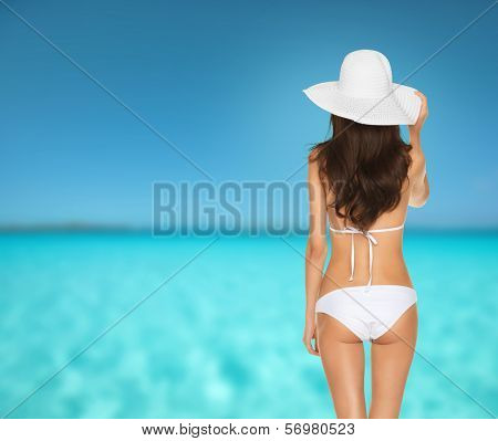 vacation, summer holidays and lingerie concept - back view of beautiful woman in white bikini and hat on a beach