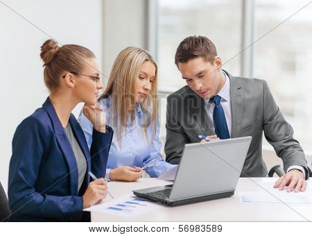 business, technology and office concept - concentrated business team with laptop computers and documents having discussion in office