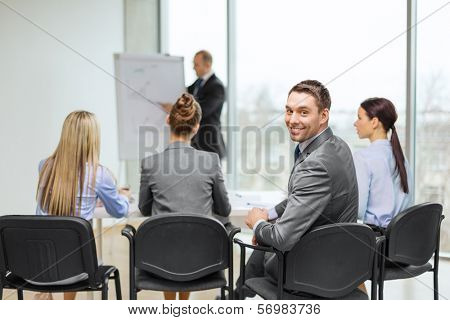 business, office and success concept - confident businessman with team in office