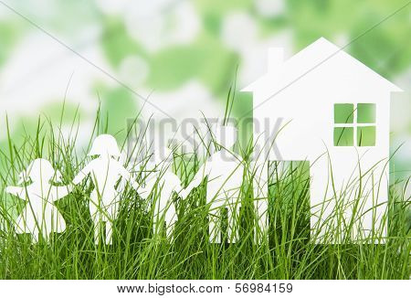 Paper cut of family with house on grass