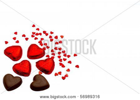 Heart-shaped Chocolate Pieces And Small Heart-shaped Deco Articles On A White Background