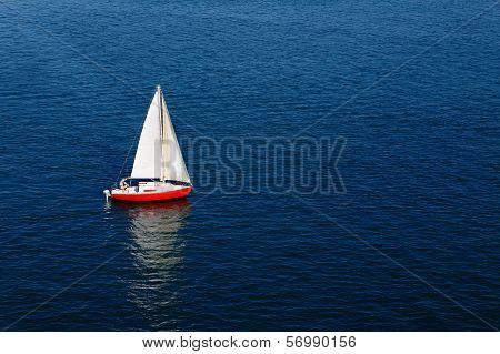 A lone white sail on a calm blue sea
