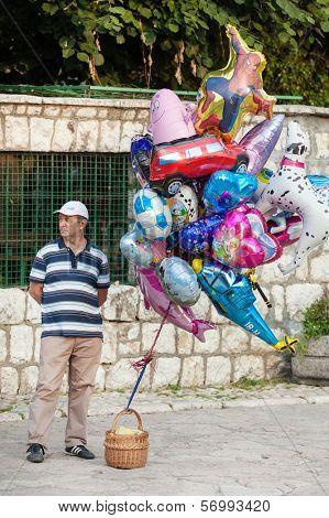 SARAJEVO, BOSNIA AND HERZEGOVINA - AUGUST 13, 2012: Man sells helium balloons on Bascarsija, the old town, very popular tourist place.