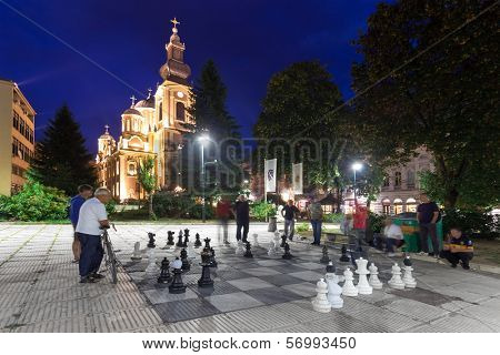 SARAJEVO, BOSNIA AND HERZEGOVINA - AUGUST 13, 2012: Men play chess on the street with large chess pieces at night with church in background.