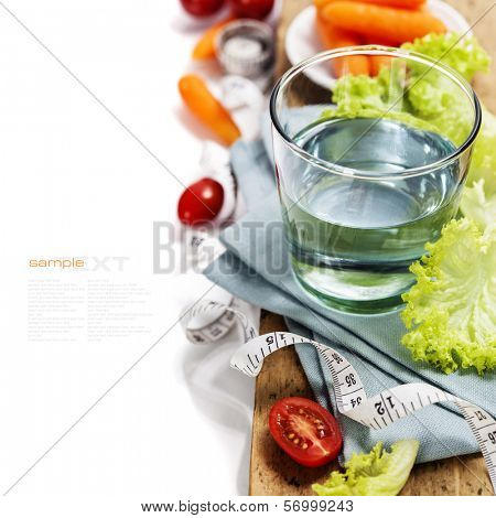Fresh vegetables and measurement tape - diet and healthy eating concept - over white (with easy removable sample text)